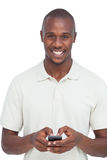 Uomo sorridente che per mezzo del suo telefono cellulare Fotografie Stock Libere da Diritti
