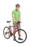 Uomo sorridente che propone con una bici di montagna Fotografia Stock