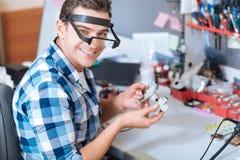 Uomo sorridente che ripara i dettagli della macchina fotografica del fuco Fotografia Stock