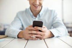 Uomo sorridente che scrive su un telefono moderno Fotografie Stock Libere da Diritti