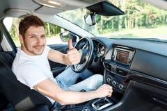Uomo sorridente che sfoglia su automobile interna fotografie stock libere da diritti