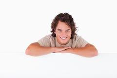 Uomo sorridente che si appoggia su un whiteboard Immagine Stock Libera da Diritti