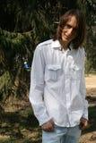 Uomo sorridente che si leva in piedi sotto un albero di abete Fotografie Stock