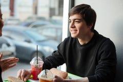 Uomo sorridente che si siede in caffè con il suo succo bevente della sorella Fotografie Stock Libere da Diritti