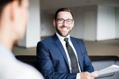 Uomo sorridente che si siede e che esamina persona fotografie stock