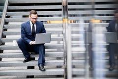 Uomo sorridente che si siede sui punti con il computer portatile e la tazza della bevanda calda immagini stock libere da diritti