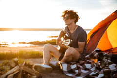 Uomo sorridente che si siede vicino alla tenda turistica ed a giocare chitarra immagine stock