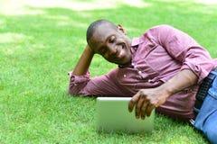 Uomo sorridente che si trova sul prato inglese con la compressa Immagini Stock