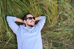 Uomo sorridente che si trova sull'erba Immagini Stock Libere da Diritti