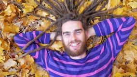 Uomo sorridente che si trova sulle foglie cadute nel parco di autunno archivi video