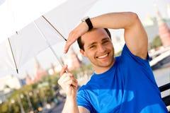 Uomo sorridente che tiene ombrello bianco all'aperto Fotografia Stock Libera da Diritti