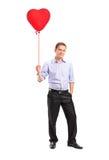 Uomo sorridente che tiene un aerostato rosso Fotografie Stock