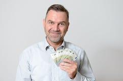 Uomo sorridente che tiene un fan di cinque euro note Fotografie Stock Libere da Diritti