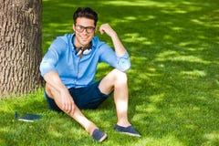Uomo sorridente che tiene un libro e una o sorridente l'erba Immagini Stock