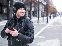 Uomo sorridente che utilizza applicazione di musica nel suo smartphone Inverno Fotografie Stock Libere da Diritti