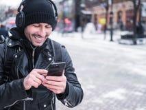 Uomo sorridente che utilizza applicazione di musica nel suo smartphone Inverno Immagini Stock