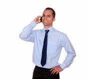 Uomo sorridente che vi esamina che parlate sul cellulare Immagine Stock