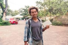 Uomo sorridente con i libri di condizione e della tenuta dello zaino all'aperto Fotografia Stock Libera da Diritti