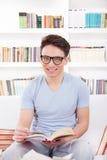 Uomo sorridente con i vetri che legge un libro sullo strato Immagini Stock