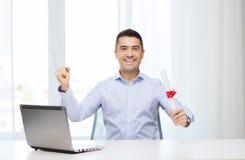 Uomo sorridente con il diploma ed il computer portatile all'ufficio Fotografia Stock