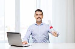 Uomo sorridente con il diploma ed il computer portatile all'ufficio Immagini Stock Libere da Diritti