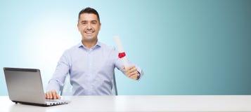Uomo sorridente con il diploma ed il computer portatile alla tavola Immagine Stock Libera da Diritti