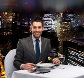 Uomo sorridente con il piatto principale di cibo del pc della compressa Fotografie Stock