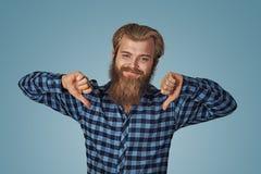 Uomo sorridente con il pollice giù Tipo allegro che esprime disapprovazione immagine stock libera da diritti