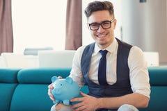 Uomo sorridente con il porcellino salvadanaio in nuovo appartamento fotografia stock libera da diritti