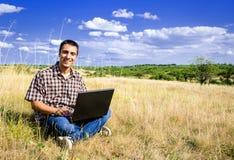 Uomo sorridente con il suo computer portatile Immagine Stock Libera da Diritti
