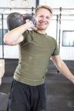 Uomo sorridente con kettlebell alla palestra di forma fisica Immagini Stock