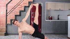 Uomo sorridente con l'esercizio di pratica di yoga dell'ente esile perfetto a casa che esamina la foto a figura intera della macc video d archivio