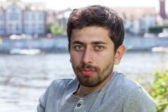 Uomo sorridente con la barba in una camicia grigia su un fiume Fotografie Stock Libere da Diritti