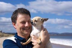 Uomo sorridente con la chihuahua sulla spiaggia Fotografia Stock Libera da Diritti