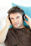 Uomo sorridente con le cuffie che ascolta la musica immagini stock