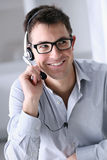 Uomo sorridente con le cuffie in ufficio, call center immagine stock