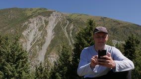 Uomo sorridente con le reti internet praticanti il surfing del telefono cellulare nel paesaggio della montagna archivi video