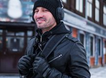 Uomo sorridente con lo zaino che cammina sulla via e che ascolta la musica tramite cuffie fotografie stock libere da diritti