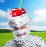 Uomo sorridente con panna montata e una ciliegia Immagine Stock