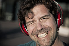 Uomo sorridente in cuffie rosse Fotografia Stock