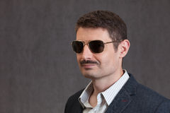 Uomo sorridente degli anni quaranta con i baffi e gli occhiali da sole Fotografie Stock
