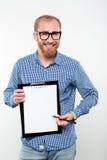 Uomo sorridente dei pantaloni a vita bassa che mostra lavagna per appunti in bianco Fotografie Stock