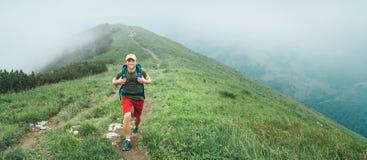 Uomo sorridente della viandante che cammina dal percorso nuvoloso nebbioso della catena montuosa del tempo con lo zaino Backpacki fotografie stock