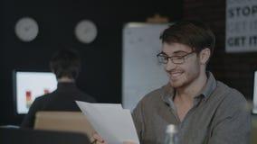 Uomo sorridente di affari che guarda la carta del documento sul posto di lavoro in ufficio scuro stock footage