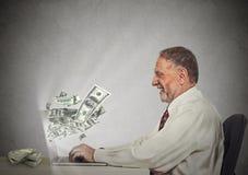 Uomo sorridente di affari che lavora online sui soldi dei guadagni del computer Immagini Stock Libere da Diritti