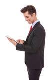 Uomo sorridente di affari che per mezzo del suo calcolatore del ridurre in pani Fotografie Stock Libere da Diritti