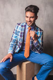 Uomo sorridente di affari che si siede su una scatola di legno Fotografia Stock Libera da Diritti