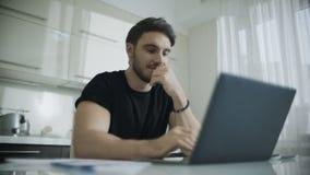 Uomo sorridente facendo uso del computer portatile al tavolo da cucina Giovane sorridere dell'uomo di affari stock footage