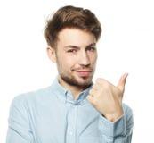 Uomo sorridente felice che mostra pollice sul segno della mano su fondo bianco Fotografie Stock