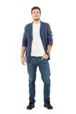 Uomo sorridente felice in jeans e camicia del denim con la mano in tasca che esamina macchina fotografica Fotografia Stock Libera da Diritti